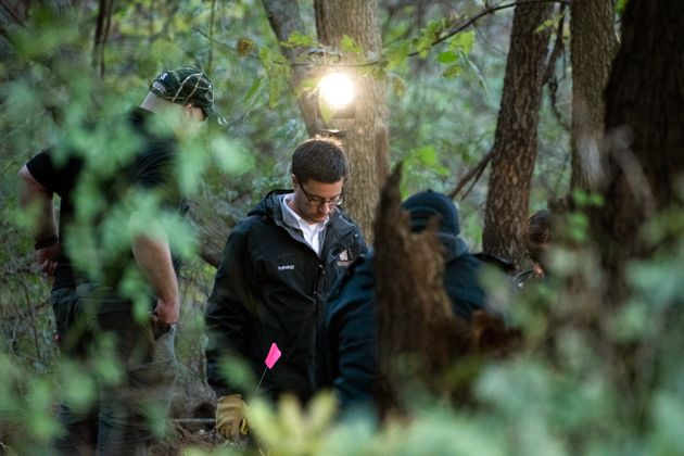 In this Monday, Oct. 22, 2018 photo, detectives investigate the scene where the remains of a southwestern...