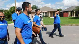 Danny Diaz, in the foreground, leads a group of neighborhood canvassers to mobilize low-propensity Latino voters in McAllen, Texas, ahead of the 2018 midterm elections.
