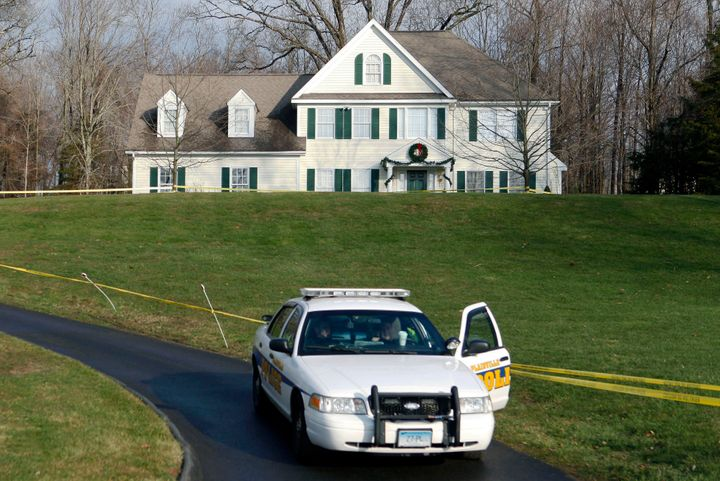 In this Dec. 18, 2012, file photo, a police cruiser sits in the driveway of the Colonial-style house where Adam Lanza lived w
