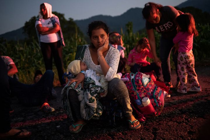 A migrant woman rests roadside with her child while traveling with a caravan of thousands from Central America en route to th