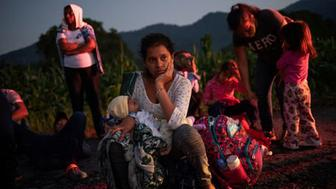 A migrant woman rests roadside with her child while traveling with a caravan of thousands from Central America en route to the United States as they make their way to Mapastepec from Huixtla, Mexico October 24, 2018. REUTERS/Adrees Latif