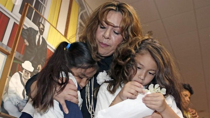 A woman comforts two children under her legal guardianship in Miami last year. One in five children being raised by extended