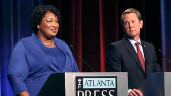 FILE - In this Tuesday, Oct. 23, 2018 file photo, Democratic gubernatorial candidate for Georgia Stacey Abrams, left, speaks as her Republican opponent Secretary of State Brian Kemp looks on during a debate in Atlanta. A federal judge says Georgia election officials must stop rejecting absentee ballots and absentee ballot applications because of a mismatched signature without first giving voters a chance to fix the problem. U.S. District Judge Leigh May on Wednesday, Oct. 24, 2018 ordered the secretary of state's office to instruct county election officials to stop the practice for the November midterm elections. She outlined a procedure to allow voters to resolve alleged signature discrepancies.(AP Photo/John Bazemore, Pool, File)