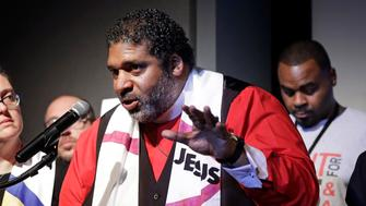 """FILE - In this April 2, 2018 file photo,  Rev. Dr. William J. Barber II, center, and Rev. Dr. Liz Theoharis, left, co-chairs of the Poor People's Campaign, speak at the National Civil Rights Museum in Memphis, Tenn. They announced the campaign is preparing for 40 days of non-violent """"direct action"""" in about 30 states that will climax with a rally in Washington this June. The organization is the rekindling of the campaign to help poor people that the Rev. Martin Luther King Jr. was working on when he was killed April 4, 1968, in Memphis. (AP Photo/Mark Humphrey)"""