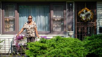 Seventy-five year old Ida Sain stands on the front porch of the home she's lived in since 1972 where a row of abandoned homes behind her property are being demolished. The city of Gary, Ind., has been successfully executing a program to demolish abandoned homes throughout the city, Wednesday, Sept. 19, 2018.