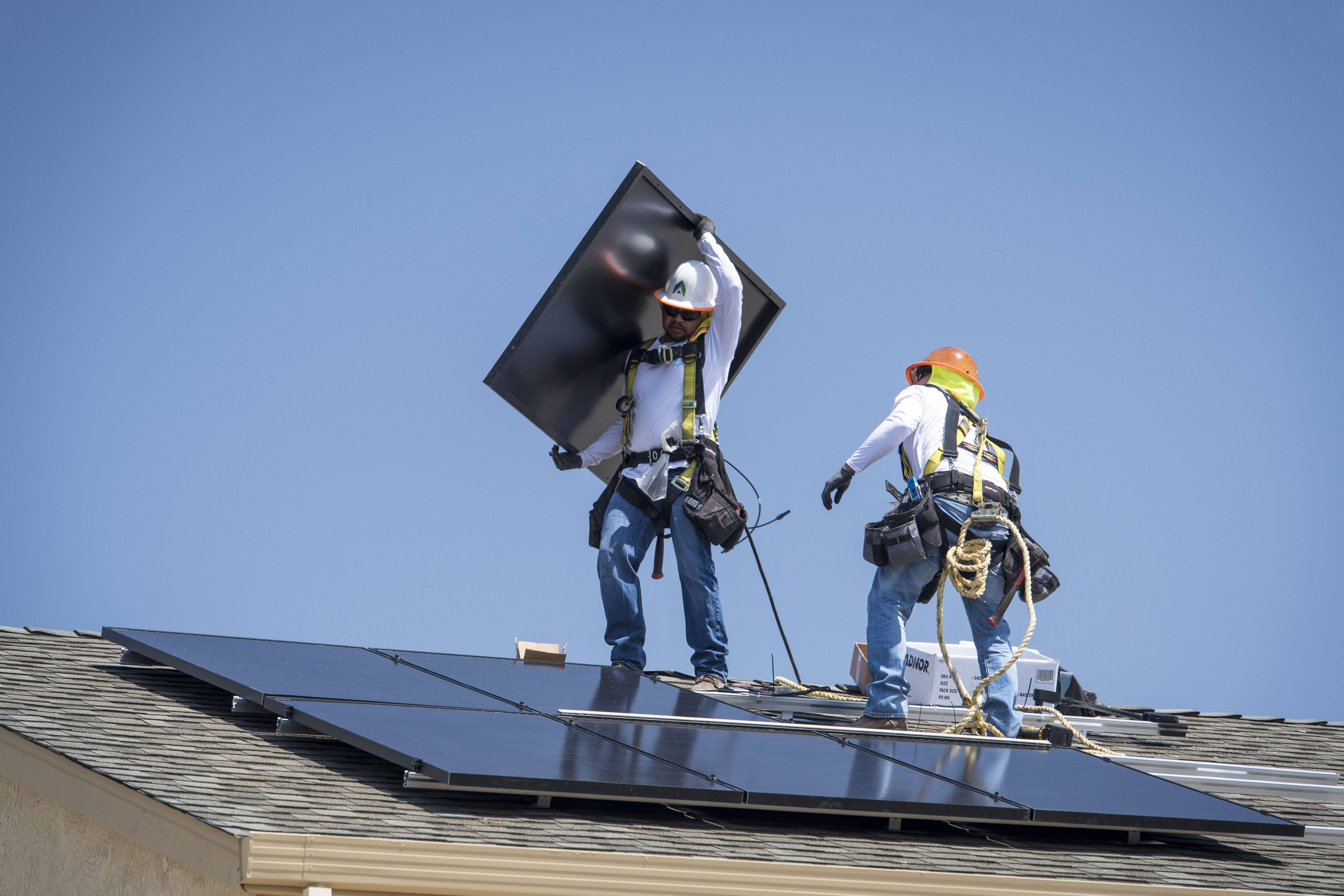 Contractors install SunRun Inc. solar panels on the roof of a new home at the Westline Homes Willowood Cottages community in Sacramento, California, U.S., on Wednesday, Aug. 15, 2018. California is the first state in the U.S. to require solar panels on almost all new homes as part of a mandate to take effect in 2020. Photographer: David Paul Morris/Bloomberg via Getty Images