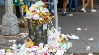 New York, United States, August 18, 2018:An overflowing trash can on the streets of Manhattan New York, with garbage sitting on the ground. Trash heaps on the street contribute to New York's rat problem.