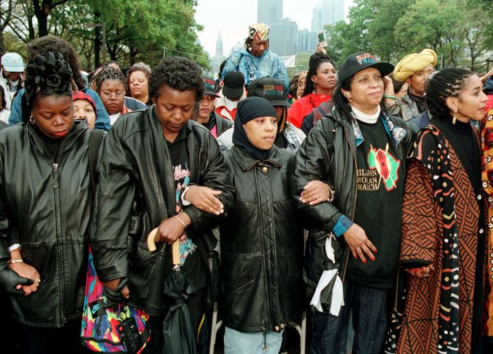 Women link arms in prayer during the 1997 Million Woman March.