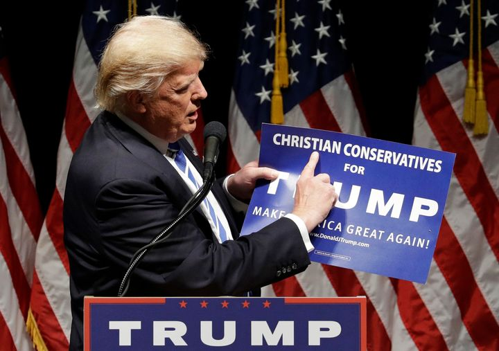 "Then-presidential candidate Donald Trump holds up a ""Christian Conservatives for Trump"" sign at a rally on Sept. 28, 2016, in"