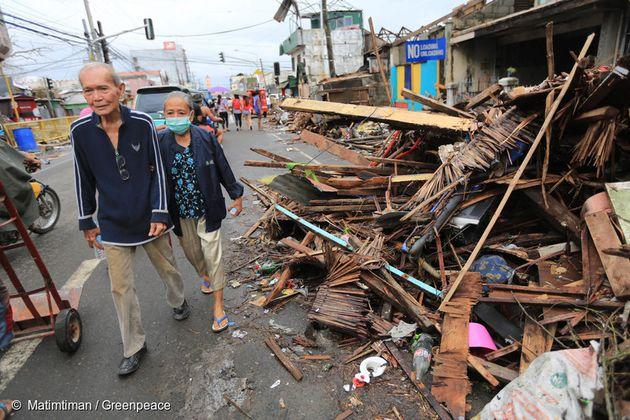 2013년 타클로반 시에서 노부부가 태풍 하이옌이 휩쓴 거리를 지나가고