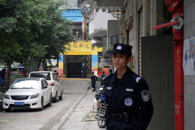 Police officers are seen outside the gate of a kindergarten where a woman armed with a kitchen knife...