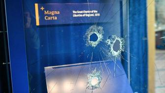 Hammer holes in the glass case that housed the Magna Carta, at Salisbury Cathedral after a 45-year-old man has been arrested on suspicion of its attempted theft, in Salisbury, England, Friday Oct. 26, 2018. British police said Friday that cathedral alarms sounded Thursday when a person tried to smash the glass display box surrounding the Magna Carta in Salisbury Cathedral, and a man has been arrested. (Ben Birchall/PA via AP)