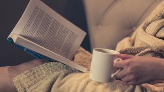 Close up of woman drinking tea and reading a book at night at home.