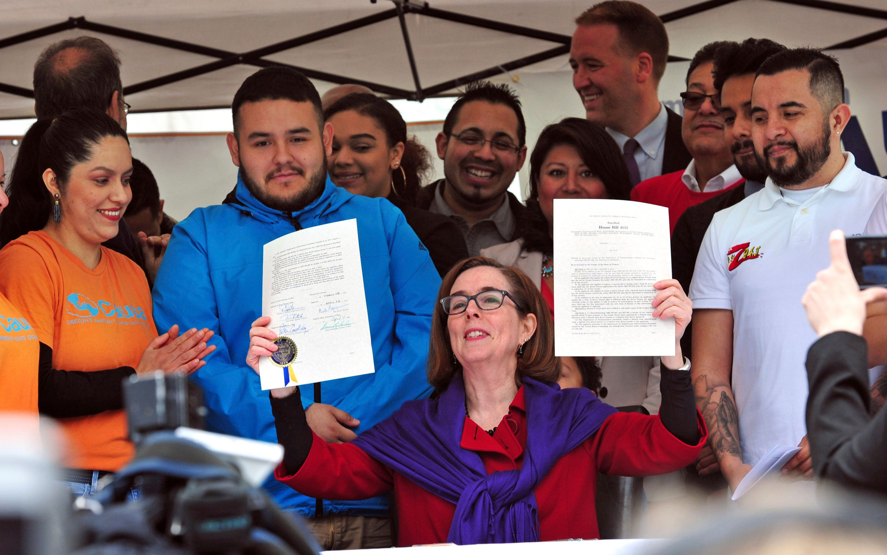 Oregon Gov. Kate Brown holds up a ceremonial copy of an immigration-related bill during a May Day rally at the steps of the state Capitol in Salem on Tuesday, May 1, 2018. A crowd of about 300 assembled for the rally and a subsequent march through downtown Salem. (AP Photo/Tom Tait)