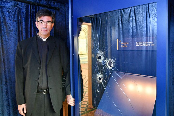 The Very Rev. Nick Papadopoulos stands next to the damaged glass case.