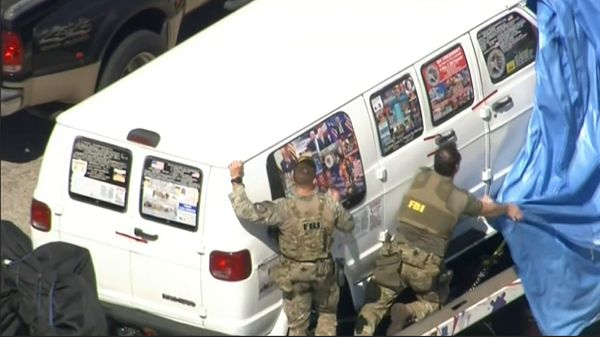 This frame grab from video provided by WPLG-TV shows FBI agents covering the van after the tarp fell off as it was transporte