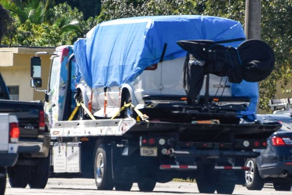 A van covered in blue tarp is towed by FBI investigators on October 26, 2018, in Plantation, Florida, in connection with the