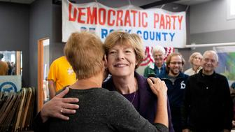 U.S. Sen. Tammy Baldwin, D-Wis., center, hugs state Rep. Deb Kolste during a campaign event, Tuesday, Oct. 16, 2018, at the Democratic Party of Rock County office in downtown Janesville, Wis. Baldwin has outraised her Republican opponent state Sen. Leah Vukmir more than 2-to-1 for the most recent reporting period. (Angela Major/The Janesville Gazette via AP)
