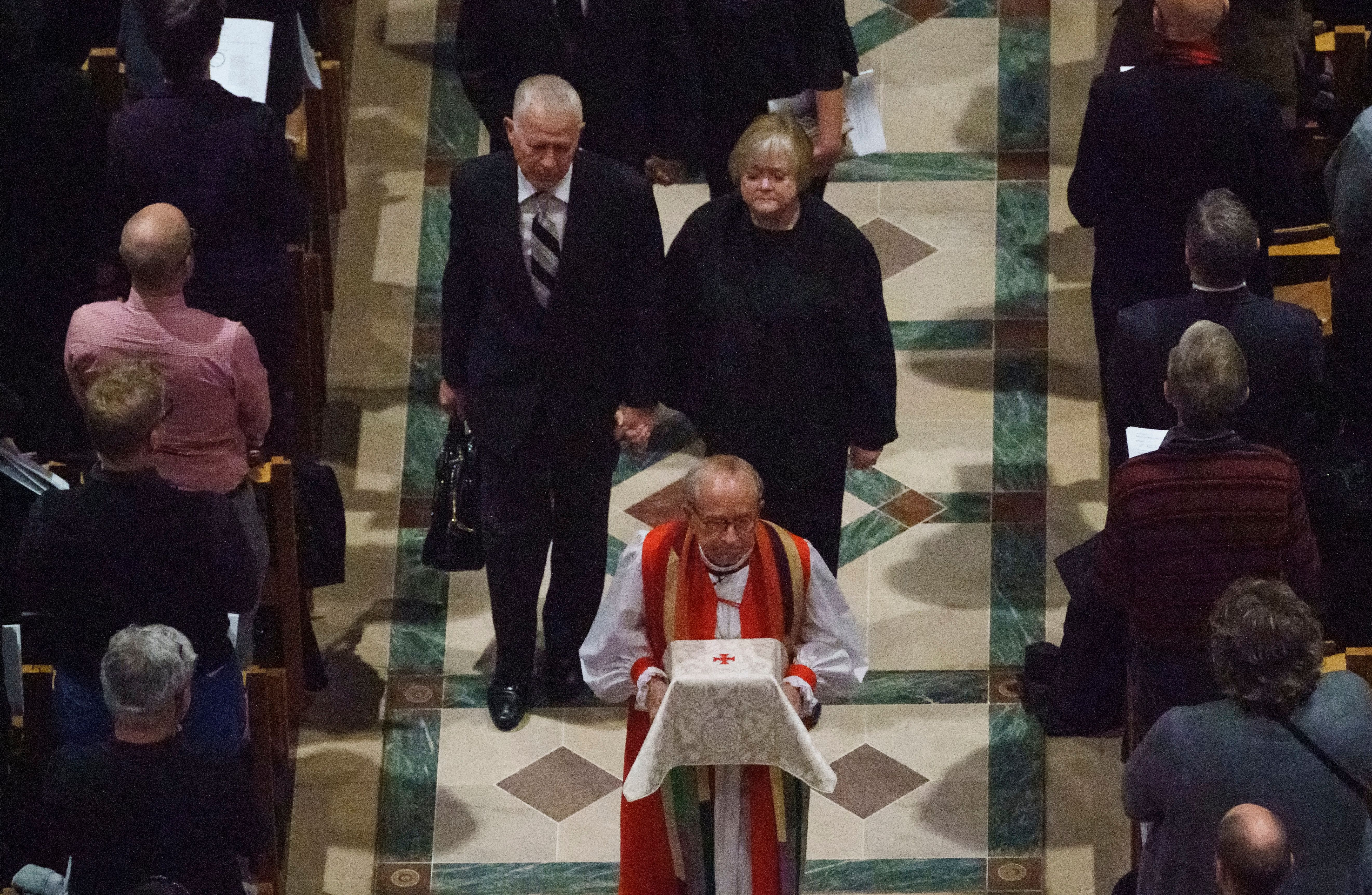 """Dennis and Judy Shepard hold hands as they walk behind Rev. V. Gene Robinson carrying their son's ashes during the at the conclusion of a """"Thanksgiving and Remembrance of Matthew Shepard"""" service at Washington National Cathedral in Washington, Friday, Oct. 26, 2018. The ashes of Matthew Shepard, whose brutal murder in the 1990s became a rallying cry for the gay rights movement, will be laid to rest in Washington National Cathedral. (AP Photo/Carolyn Kaster)"""