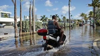 A motorbike navigates through floodwater caused by a seasonal king tide, Monday, Oct. 17, 2016, in Hollywood, Fla. King tides bring in unusually high water levels and can cause local tidal flooding. (AP Photo/Lynne Sladky)