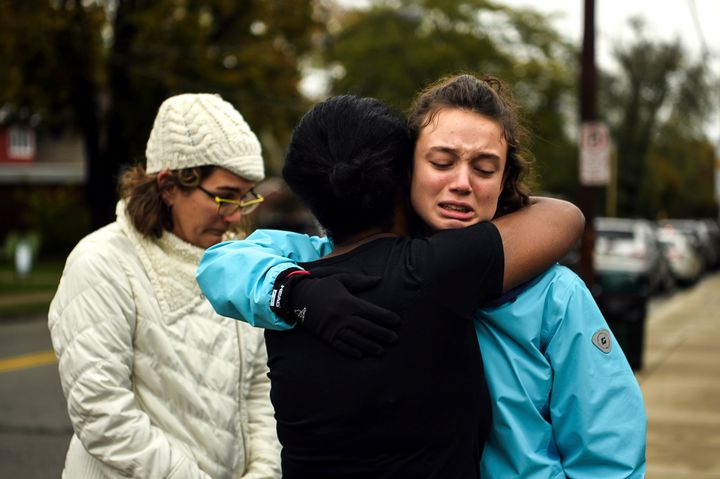 From left, Kate Rothstein looks on as Tammy Hepps hugs Simone Rothstein, 16, on the intersection of Shady Avenue and Northumb