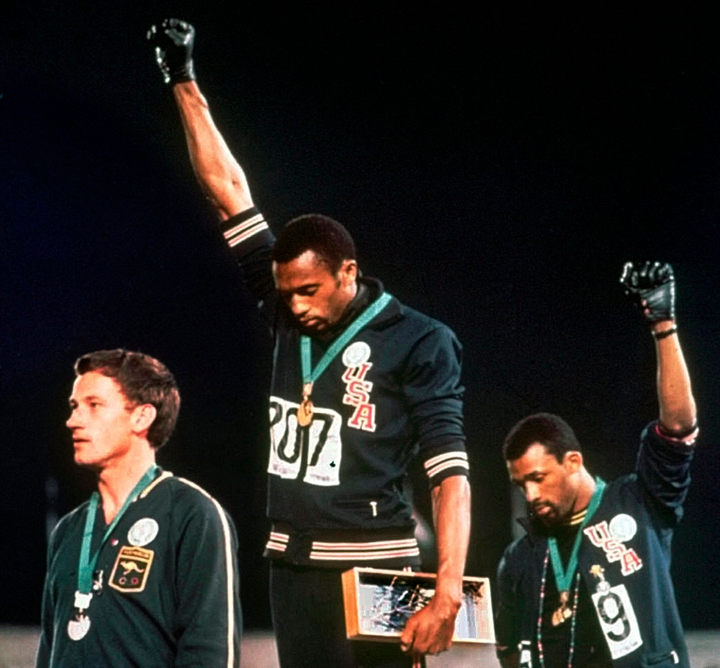 FILE - In this Oct. 16, 1968, file photo, Australian silver medalist Peter Norman, left, stands on the podium as Americans Tommie Smith, center, and John Carlos raise their gloved fists in a human rights protest. Australian Olympic Committee (AOC) awarded on Saturday, April 28, 2018, a posthumous Order of Merit to Norman. AOC President John Coates said that Norman's achievements as an athlete - his silver-medal winning time of 20.06 seconds at Mexico City remains an Australian record 50 years after he set the mark - were dwarfed by his support for the gold and bronze medalists who raised their gloved fists and bowed their heads during the American national anthem. (AP Photo, File)
