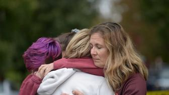 From left Cody Murphy, 17 Sabrina Weihrauch, and Amanda Godley, left, all of Pittsburgh, hug after an active shooter situation at Tree of Life Synagogue on Saturday, Oct. 27, 2018. Multiple casualties have been reported at the synagogue. (Andrew Stein/Pittsburgh Post-Gazette via AP)