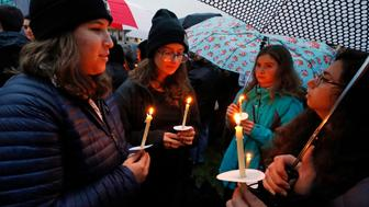 Holding candles, a group of girls wait for the start of a memorial vigil at the intersection of Murray Ave. and Forbes Ave. in the Squirrel Hill section of Pittsburgh, for the victims of the shooting at the Tree of Life Synagogue where a shooter opened fire, killing multiple people and wounding others, including several police officers, Saturday, Oct. 27, 2018. (AP Photo/Gene J. Puskar)