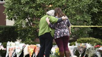 Women embrace in front of memorial flowers on October 28, 2018 outside of the Tree of Life Synagogue after a shooting there left 11 people dead in the Squirrel Hill neighborhood of Pittsburgh on October 27, 2018. - A man suspected of bursting into a Pittsburgh synagogue during a baby-naming ceremony and gunning down 11 people has been charged with murder, in the deadliest anti-Semitic attack in recent US history. The suspect -- identified as a 46-year-old Robert Bowers -- reportedly yelled 'All Jews must die' as he sprayed bullets into the Tree of Life synagogue during Sabbath services on Saturday before exchanging fire with police, in an attack that also wounded six people. (Photo by Brendan SMIALOWSKI / AFP)        (Photo credit should read BRENDAN SMIALOWSKI/AFP/Getty Images)