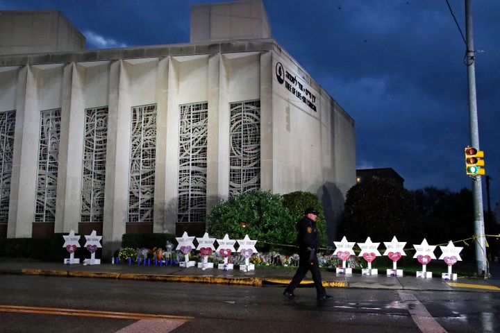 A police officer walks past the Tree of Life Synagogue and a memorial of flowers and stars in Pittsburgh on Sunday, Oct. 28,