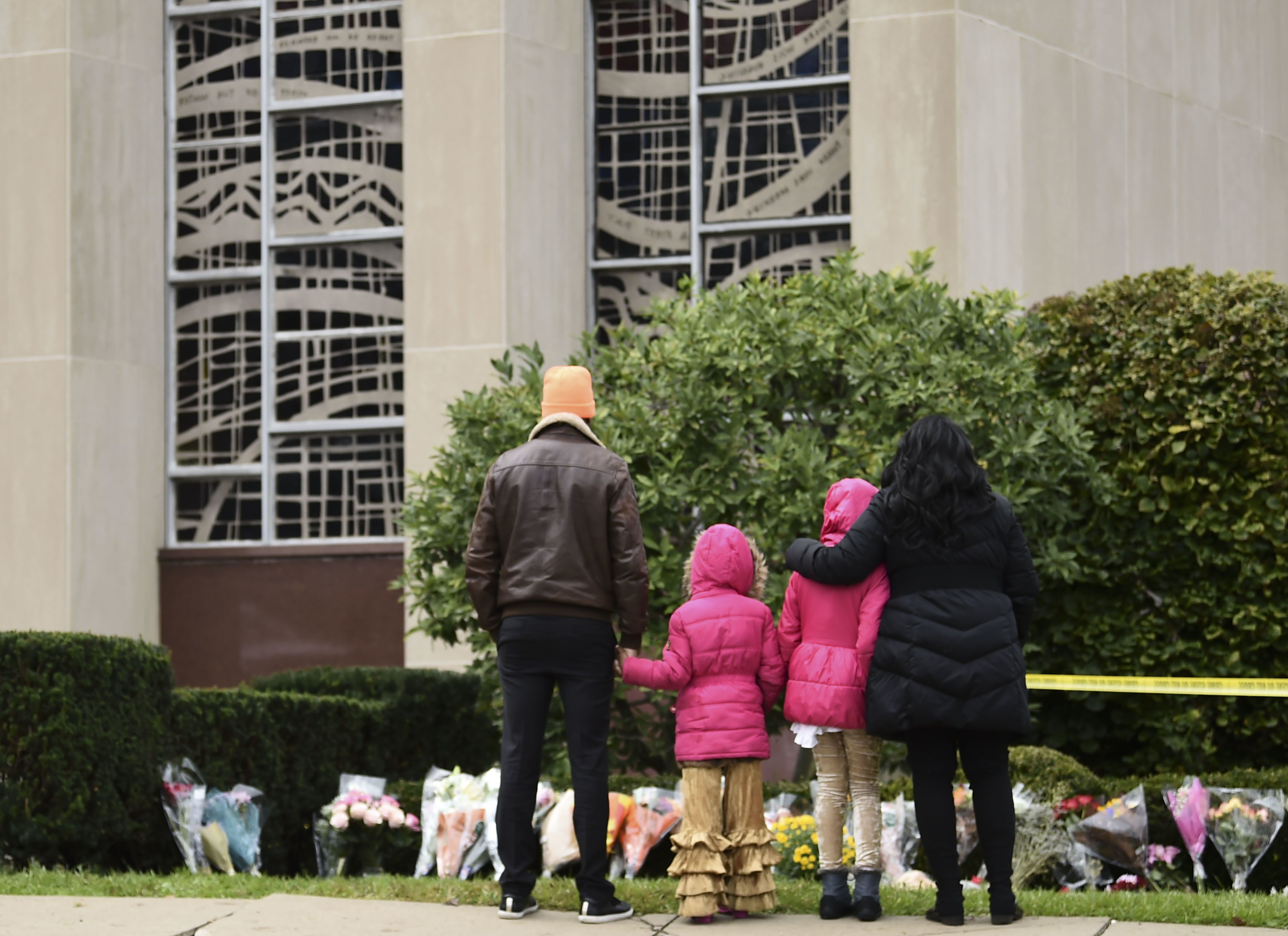 People stand in front of a memorial on October 28, 2018 outside of the Tree of Life Synagogue after a shooting there left 11 people dead in the Squirrel Hill neighborhood of Pittsburgh on October 27, 2018. - A man suspected of bursting into a Pittsburgh synagogue during a baby-naming ceremony and gunning down 11 people has been charged with murder, in the deadliest anti-Semitic attack in recent US history. The suspect -- identified as a 46-year-old Robert Bowers -- reportedly yelled 'All Jews must die' as he sprayed bullets into the Tree of Life synagogue during Sabbath services on Saturday before exchanging fire with police, in an attack that also wounded six people. (Photo by Brendan SMIALOWSKI / AFP)        (Photo credit should read BRENDAN SMIALOWSKI/AFP/Getty Images)