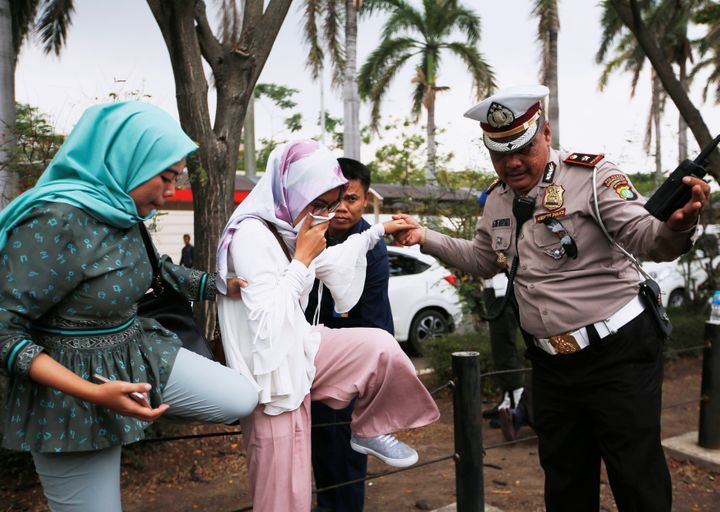 A woman is helped by a policeman as she arrives at a crisis center at Soekarno Hatta International airport near Jakarta