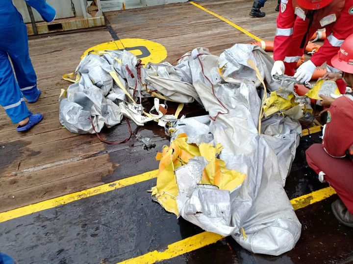 Workers examine recovered debris from what is believed to be flight JT610.