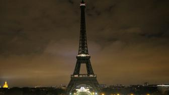 The lights of the Eiffel tower falls dark at midnight in Paris, France, Wednesday, April 5, 2017. Paris mayor Anne Hidalgo says the Eiffel Tower will fall dark overnight to honor the victims of the St. Petersburg subway bombing. (AP Photo/Michel Euler)