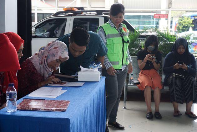 Des proches des passagers à bord de l'appareil de la compagnie indonésienne Lion Air qui...