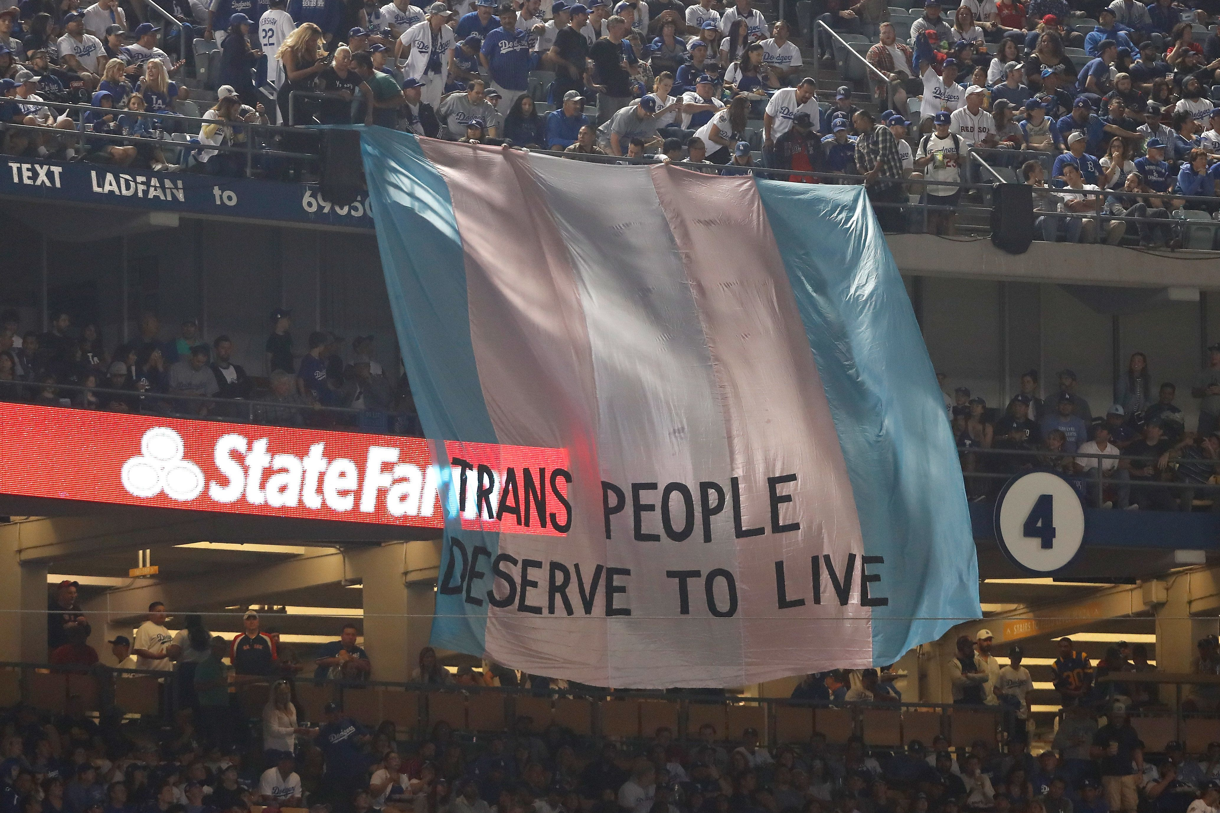 A banner with the words 'Trans People Deserve to Live' is displayed during Game Five of the 2018 World Series bet