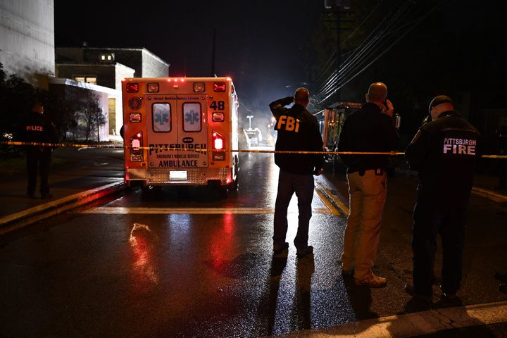 An FBI agent stands behind a police cordon and an ambulance outside the Tree of Life Synagogue (L) after a shooting there lef