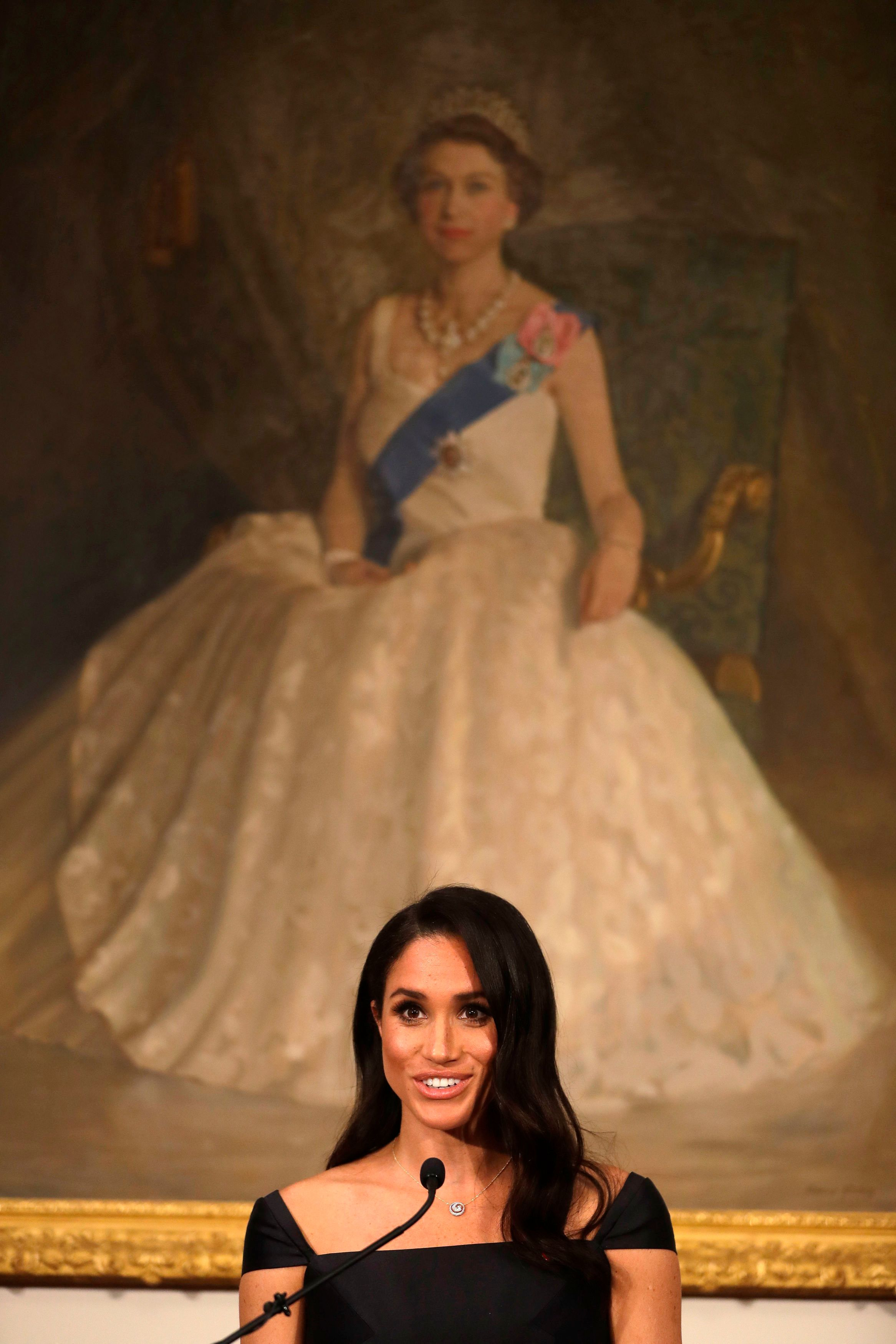 The Duchess of Sussex delivers the speech in front of a portrait of Queen Elizabeth II.