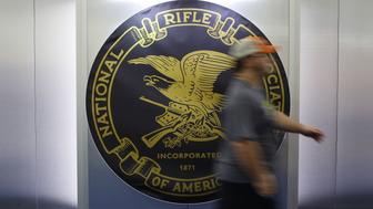 An attendee walks past a National Rifle Association (NRA) logo on the exhibit floor during the annual meeting in Louisville, Kentucky, U.S., on Friday, May 20, 2016. The nation's largest gun lobby, the NRA has been a political force in elections since at least 1994, turning out its supporters for candidates who back expanding access to guns. Photographer: Luke Sharrett/Bloomberg via Getty Images