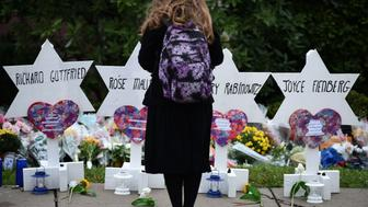 TOPSHOT - A woman stands at a memorial outside the Tree of Life synagogue after a shooting there left 11 people dead in the Squirrel Hill neighborhood of Pittsburgh on October 27. - Mourners held an emotional vigil Sunday for victims of a fatal shooting at a Pittsburgh synagogue, an assault that saw a gunman who said he 'wanted all Jews to die' open fire on a mostly elderly group. Americans had earlier learned the identities of the 11 people killed in the brutal assault at the Tree of Life synagogue, including 97-year-old Rose Mallinger and couple Sylvan and Bernice Simon, both in their 80s.Nine of the victims were 65 or older. (Photo by Brendan SMIALOWSKI / AFP)        (Photo credit should read BRENDAN SMIALOWSKI/AFP/Getty Images)