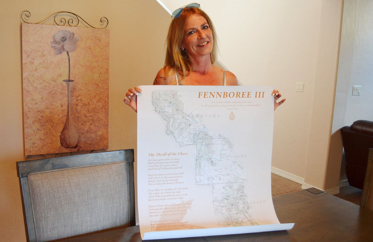 Sacha Johnston of Albuquerque holds up a poster from Fennboree, an annual gathering of Forrest Fenn treasure hunters.