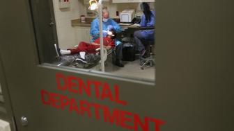An immigrant receives dental care at the Adelanto Detention Facility in 2013 in Adelanto, Californnia.