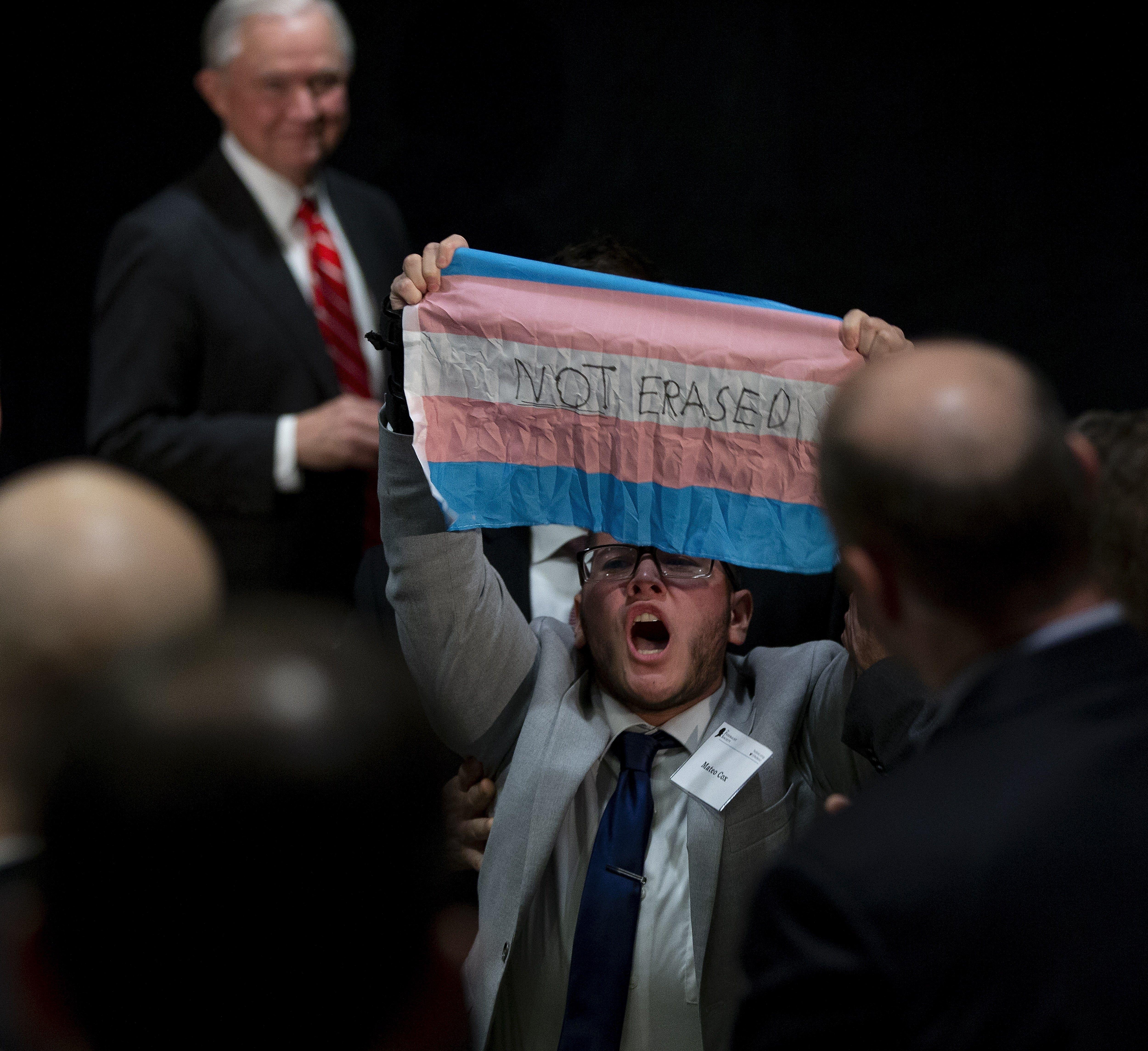 CJX13. BOSTON (ESTADOS UNIDOS), 29/10/2018.- Un manifestante muestra la bandera del orgullo transgénero durante un discurso del fiscal general estadounidense, Jeff Sessions (i), en un acto sobre la libertad religiosa en Boston (Estados Unidos) hoy, 29 de octubre del 2018. El Gobierno de Estados Unidos anunció hoy nuevos esfuerzos para combatir los crímenes de odio en el país después de la matanza en una sinagoga el pasado sábado, en la que once personas fueron asesinadas. EFE/ Cj Gunther