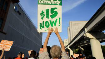 Protestors march in support of raising the minimum wage to $15 an hour as part of an expanding national movement known as Fight for 15, Wednesday, April 15, 2015, in Miami. The event was part of a national protest day to coincide with the April 15 deadline for filing income taxes. (AP Photo/Lynne Sladky)