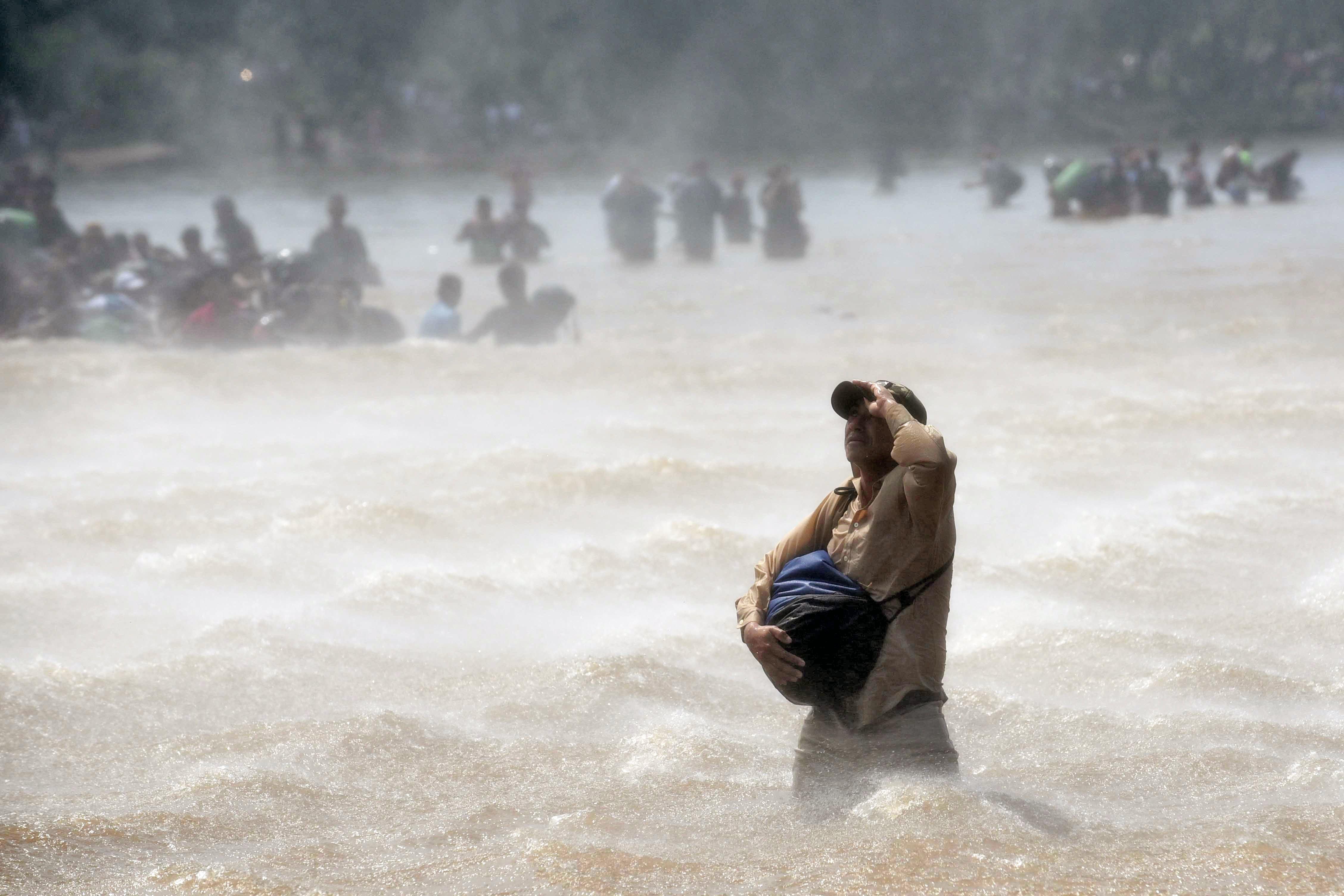 Μέσα από τα ορμητικά νερά ποταμού συνεχίζουν το ταξίδι τους για τις ΗΠΑ εκατοντάδες μετανάστες από την Ονδούρα