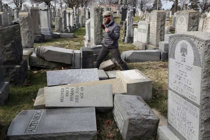 Rabbi Joshua Bolton of the University of Pennsylvania's Hillel center surveys damaged headstones at Mount Carmel Cemetery in