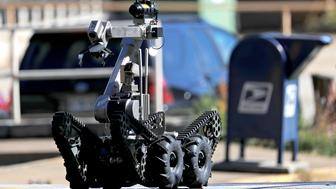 A robot exits a U.S. post office facility as law enforcement officials investigate a report that a suspicious package was found in Atlanta, Monday, Oct. 29, 2018. (AP Photo/David Goldman)