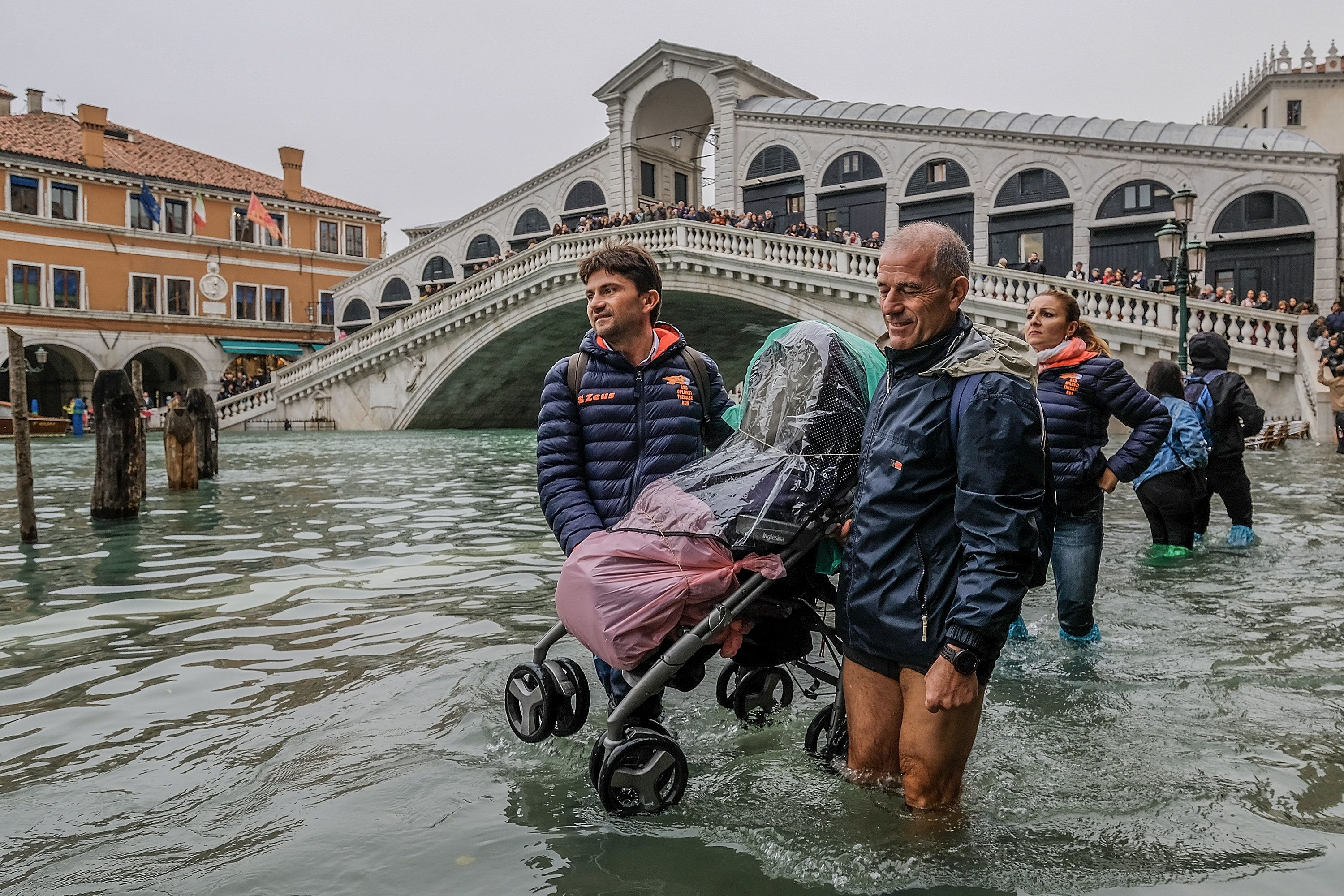 VENICE, ITALY - OCTOBER 29: Tourists carry a stroller through the flood waters on October 29, 2018 in Venice, Italy. Today due to the exceptional level of the 'acqua alta' that reaced 156 cm schools and hospitals of Venice remained closed the authorities have also advised citizens against leaving their homes  (Photo by Stefano Mazzola/Awakening/Getty Images)