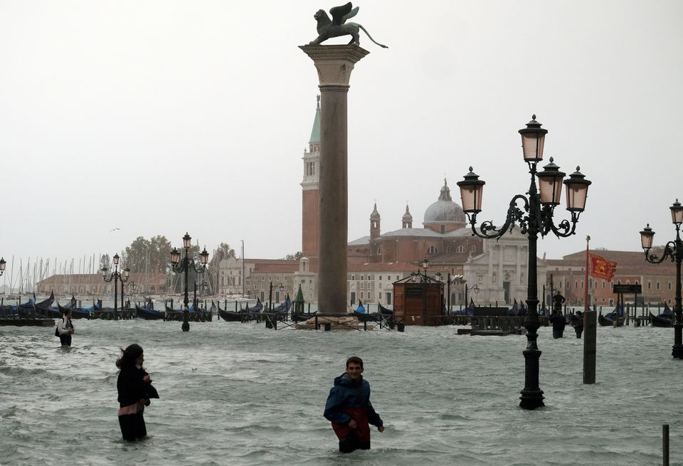 People walk in flooded Piazza San Marco during a period of seasonal high water in Venice,