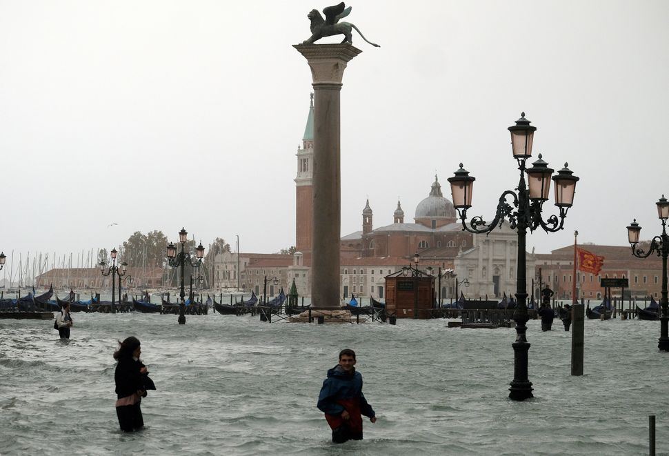 People walk in flooded Piazza San Marco during a period of seasonal high water in Venice, Italy.